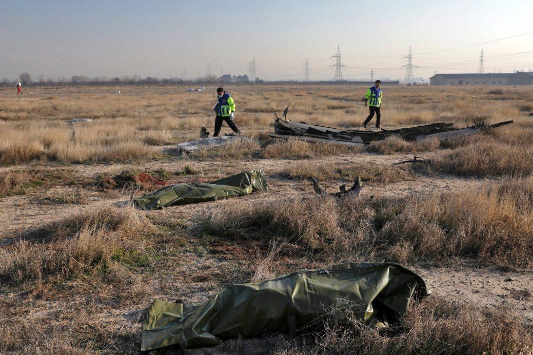 Des secouristes fouillent la scène où un avion ukrainien s'est écrasé alors que les corps des victimes dans des sacs mortuaires gisaient sur le sol, à Shahedshahr, au sud-ouest de la capitale Téhéran, Iran, le mercredi 8 janvier. - AP