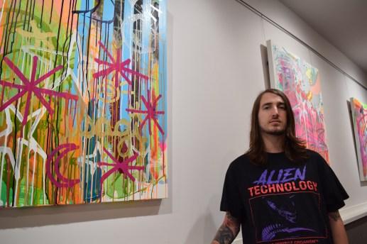 Jared Betts devant quelques-unes de ses toiles exposées à la galerie du Théâtre Capitol. - Acadie Nouvelle: Sylvie Mousseau