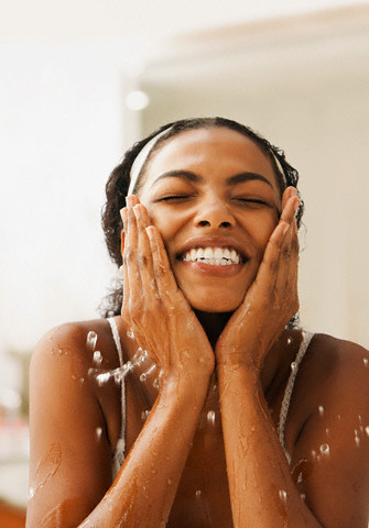 African American woman washing face --- Image by © Jose Luis Pelaez/Blend Images/Corbis