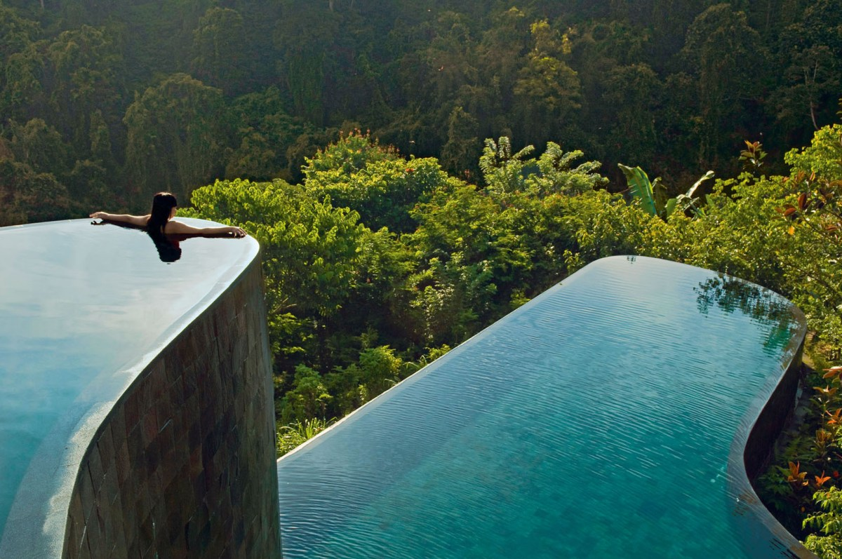 Indonesia, Bali, Gianyar, Buahan Payangan, Ubud Hanging Gardens hotel group Orient-Express, one young woman back outstretched arms, infinity pool overlooking the jungle at sunrise