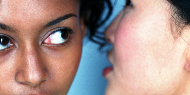 Young woman whispering in other woman's ear, close-up