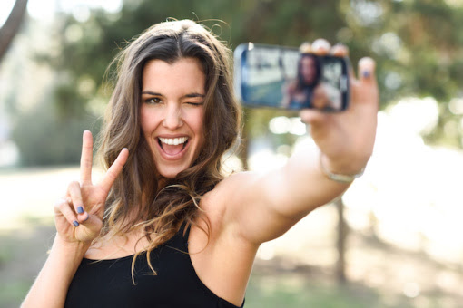 Portrait of a beautiful young woman selfie in the park with a smartphone doing v sign