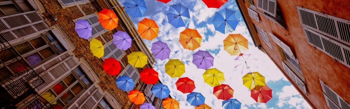 Colourful umberells hanging between buildings