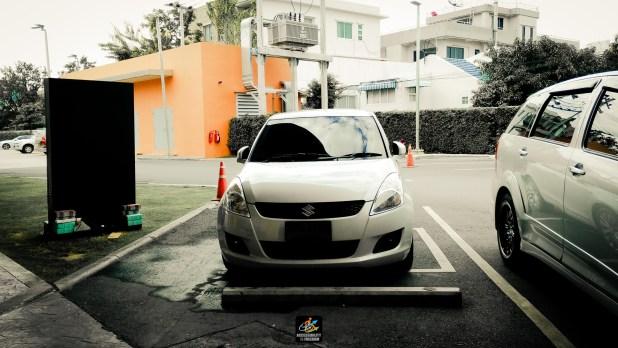 ภาพรถของซาบะ swift สีขาว จอดอยู่บนพื้นที่จอดรถนพิการ