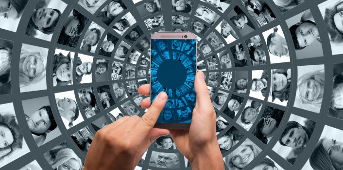 index finger tapping smartphone screen surrounded by a tunnel of images of people to demonstrate the power of access to an audience