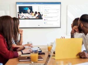 group in boardroom watching corporate webinar reviewing marketing strategies