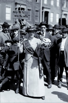 """Mrs. Suffern, wearing a sash and carrying a sign that says """"Help us to win the vote,"""" surrounded by a crowd of men and boys, ca. 1914. Photo courtesy Library of Congress/Bain News Service"""