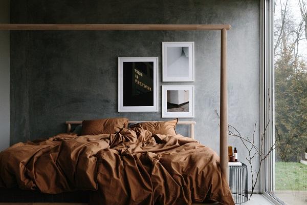 Slaapkamer met grijze wanden, houten bed, beddengoed in warm terracotta en bijzondere fotokunst aan de muur - via Accessorize your Home