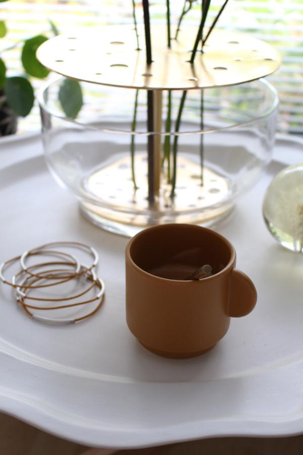 Detailfoto van de Ikebana vaas van Fritz Hansen op een wit metalen dienblad met okergeel kopje van HM Home - via Accessorize your Home