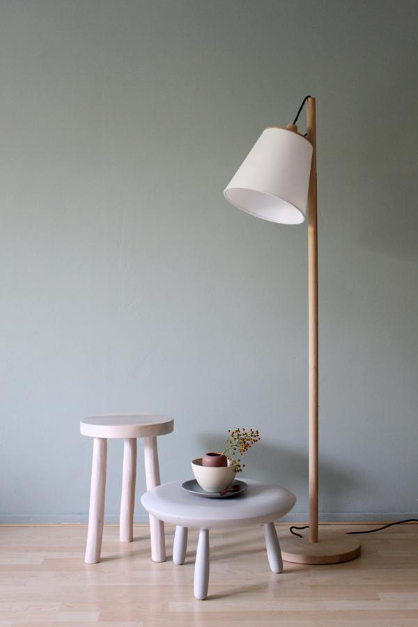Muuto Pull lamp van Flinders met houten krukjes en stapel keramiek tegen groengrijze muur van Flexa - via Accessorize your Home