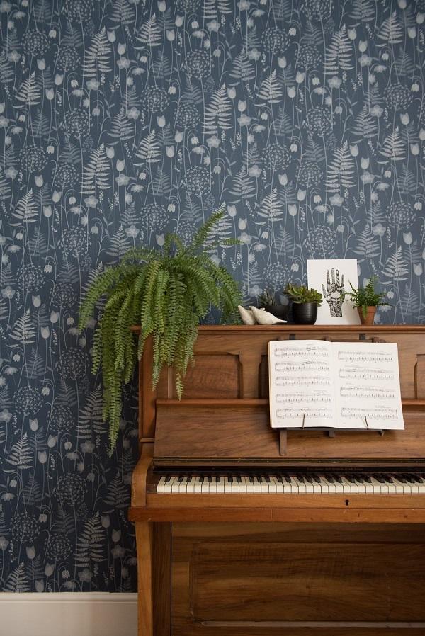 Diepblauw behang met print van lentebloemen van Hannah Nunn met piano en varen - via Accessorize your Home