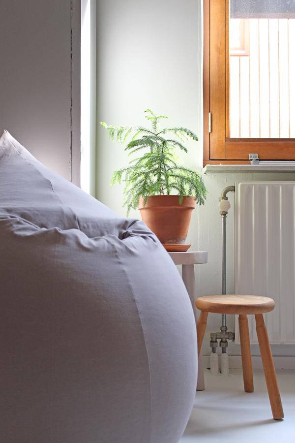 Lichtgrijze zitzak Elly met twee kleine krukjes en een plant tegen witte muur - via Accessorize your Home