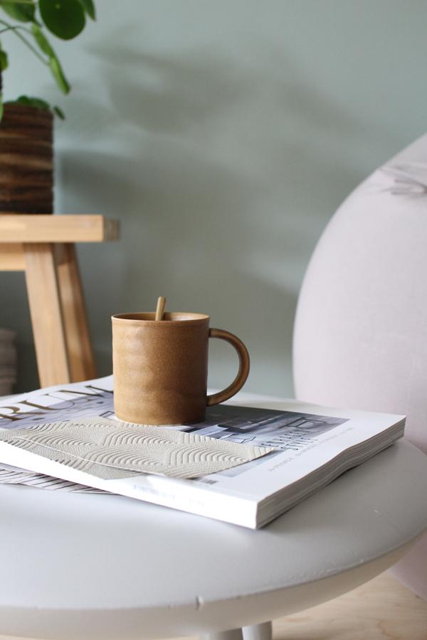 Groene muur met houten bankje en bruine koffiemok op grijs tafeltje - via Accessorize your Home