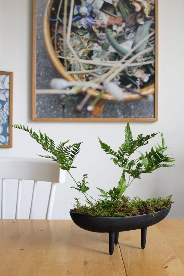 Vintage gietijzeren bloempotje met mos en varen op houten tafel met witte spijlenstoel - via Accessorize your Home