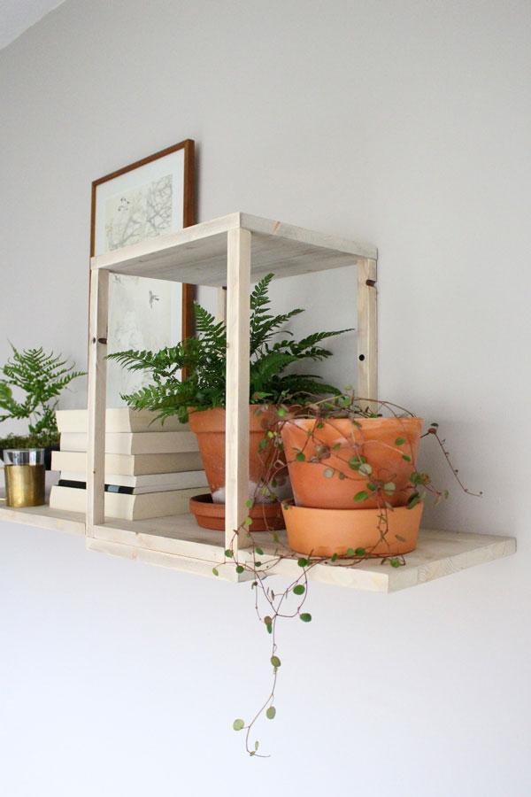 DIY zwevende wandplank met terracotta potten met planten en stapel boeken - via Accessorize your Home