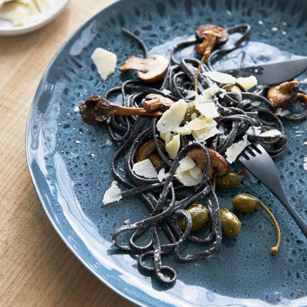 Bord voorzien van diepblauw gespikkeld glazuur met zwarte pasta en groene olijven - via Accessorize your Home