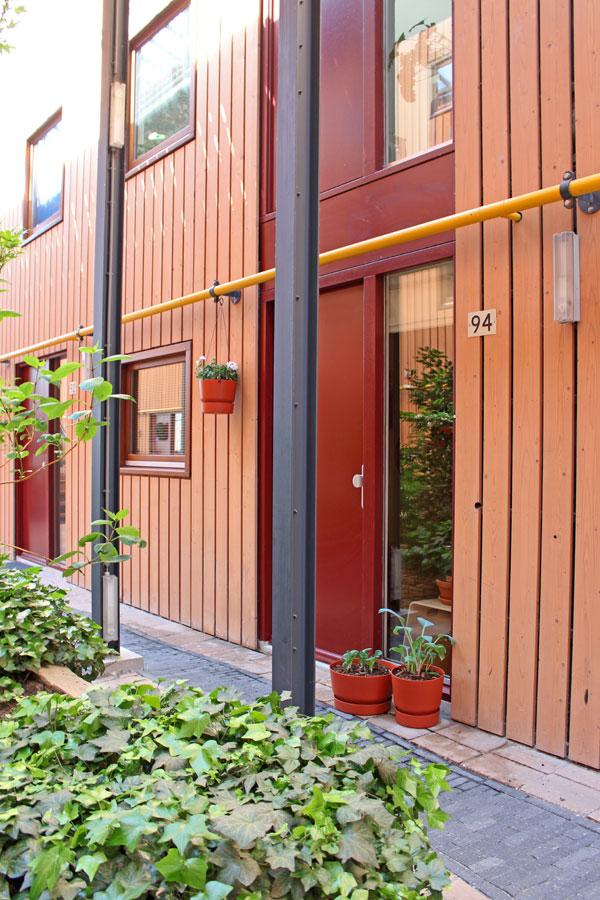 Elho Greenville buitenpotten naast rode voordeur in atrium - via Accessorize your Home