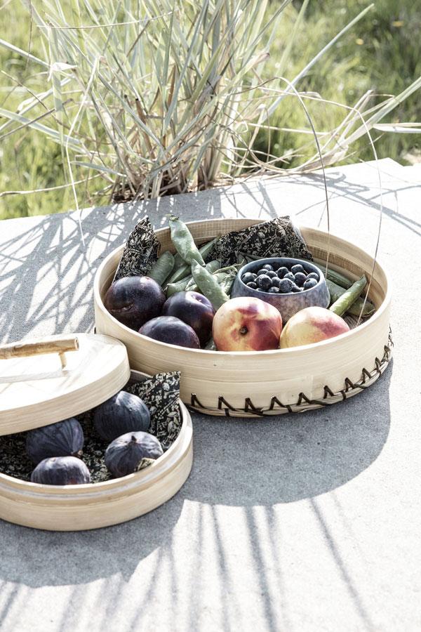 Dienbladen gemaakt van bamboe en zwart zeegras gevuld met verse vijgen en perziken.