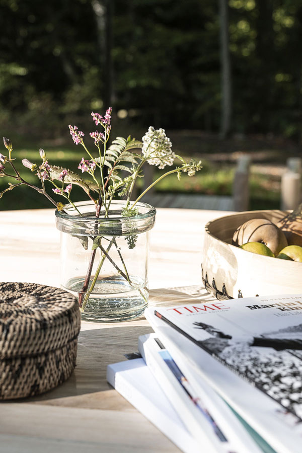 Lezen aan een zonovergoten tafel met glazen vaas van House Doctor gevuld met veldbloemen.