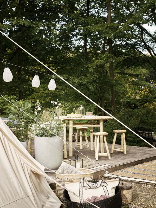 Terras naast joert met teakhouten tuinset van House Doctor en een slinger met wit katoenen lampjes.