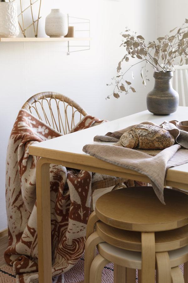 Eettafel met houten stoel met daarover een deken met mooie print - via Accessorize your Home