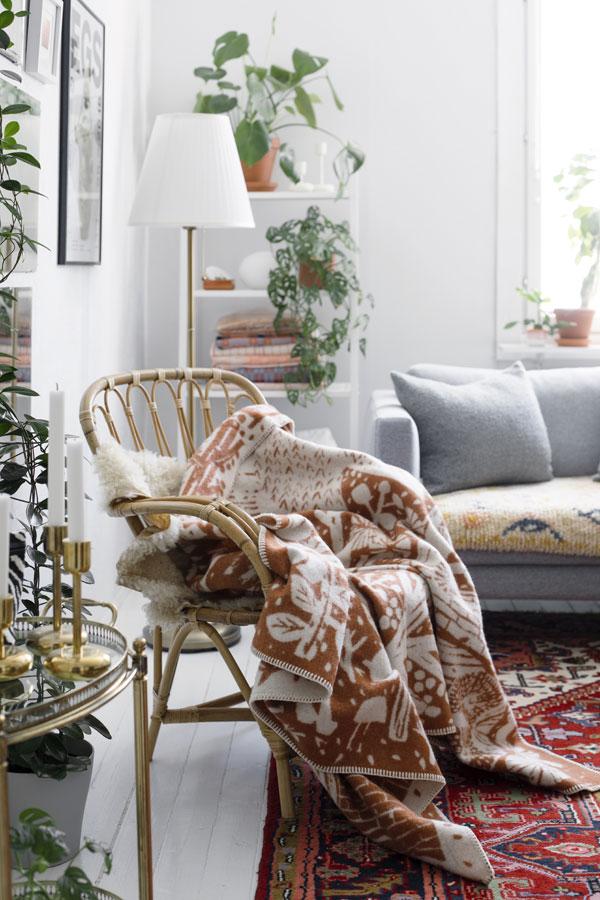 Woonkamer met rotan stoel waar een deken met print van bos overheen gedrapeerd is - via Accessorize your Home