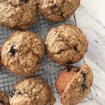 Six blueberry bran spelt muffins cooling on a wire rack, one muffin turned on its side.
