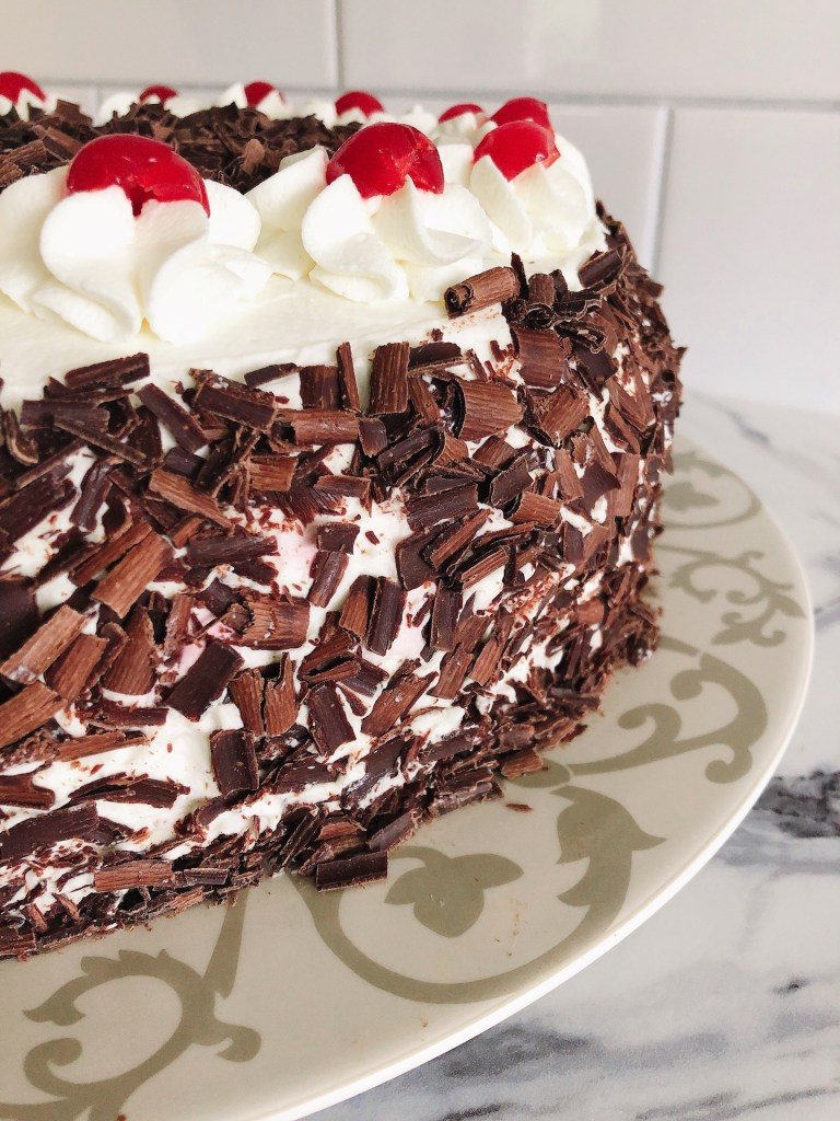 Side view of chocolate shavings and whipping cream florets with maraschino cherries on top of a black forest cake