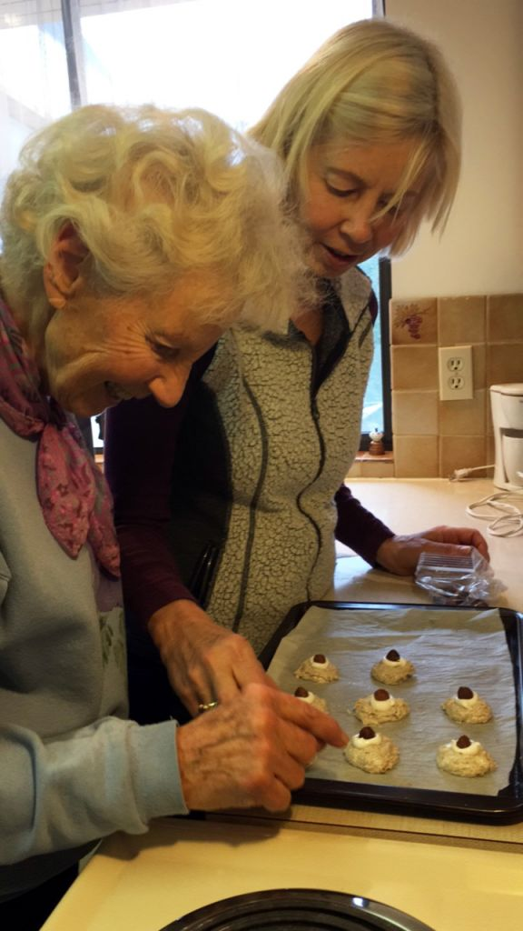 Two women in the kitchen placing hazelnut macaroons on a baking sheet