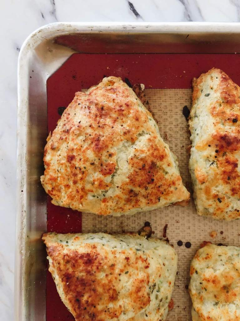 Cheddar, chive and herb spelt scones cooling on a baking tray with a silicone liner