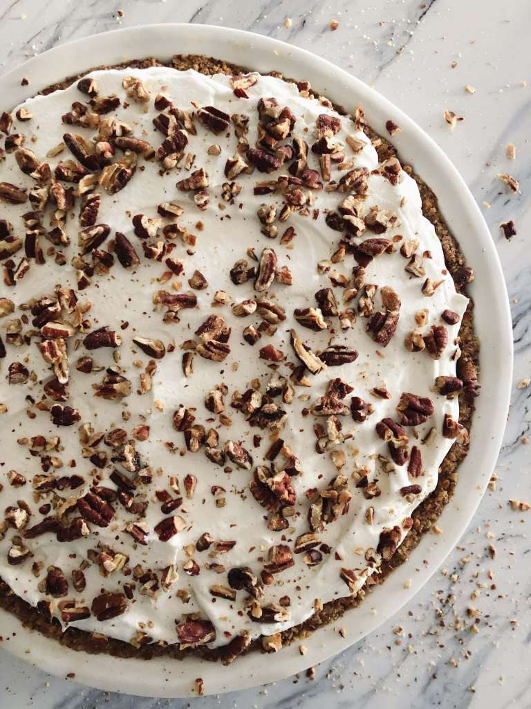 Pumpkin Pecan Torte topped with whipped cream and chopped pecans in a white pie plate on a white marble countertop
