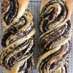 Two poppyseed stollen made from sweet yeast dough cooling on a wire rack