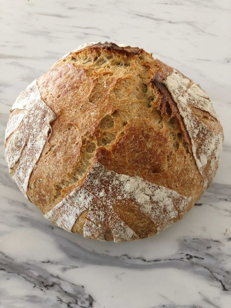 Golden brown loaf of spelt, einkorn and rye bread sitting on the countertop