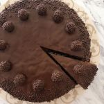 A chocolate truffle cake with one slice cut out