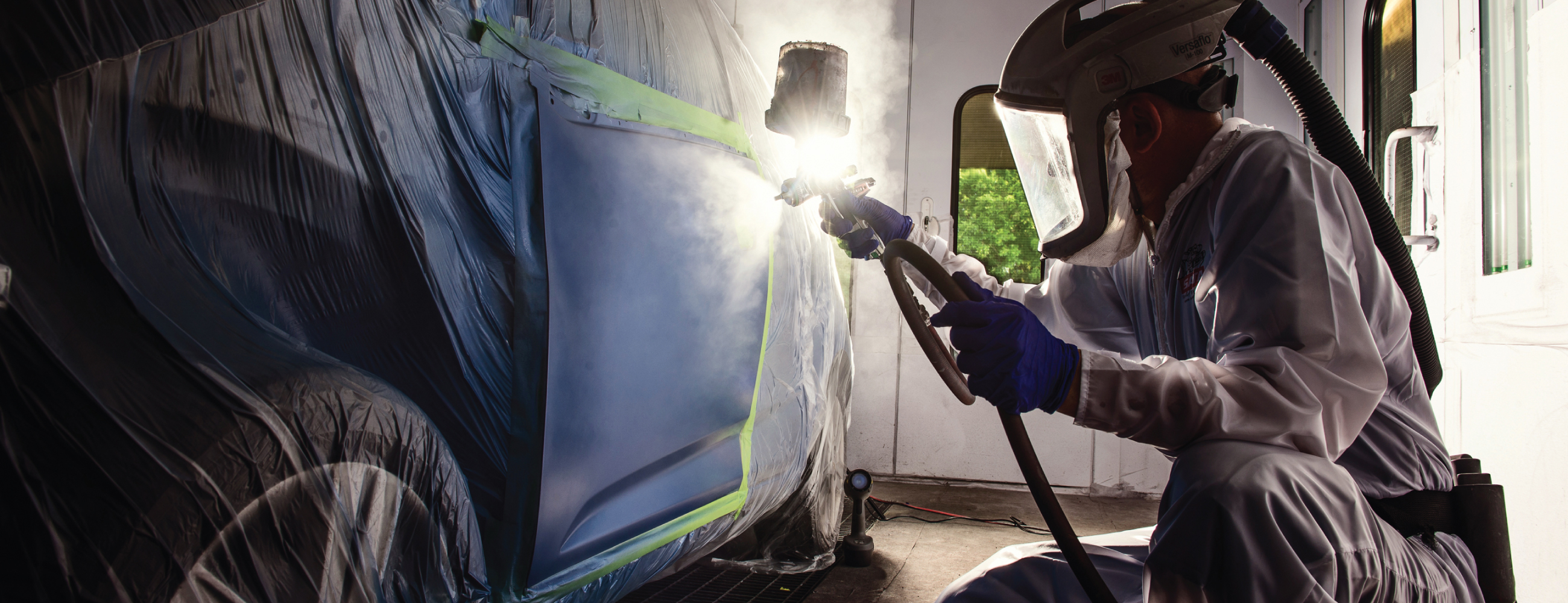 Painter using Accudraft TITAN Downdraft Paint Booth