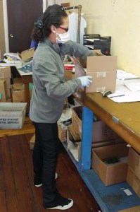 A woman packing a box wearing a face mask and gloves