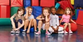 Gruppe Kinder sitzt in Turnhalle