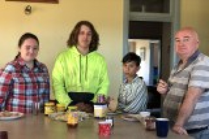 Father and three children stand around breakfast table