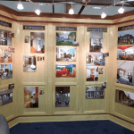 photo of free standing three section paneled wood wall with photos affixed in each panel area showing work by Acheson Builders