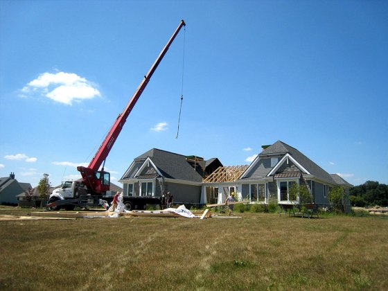 photo of fully deployed crane ready to lift materials onto fire damaged house being restored by Acheson Builders