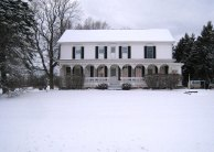 photo of two-story Acheson country house with full-width fancy-cut wooden post front porch in winter with snow blanketing front yard
