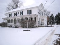 three-quarter front angle photo of two-story Acheson country house with full-width fancy-cut wooden post front porch in winter with snow blanketing front yard
