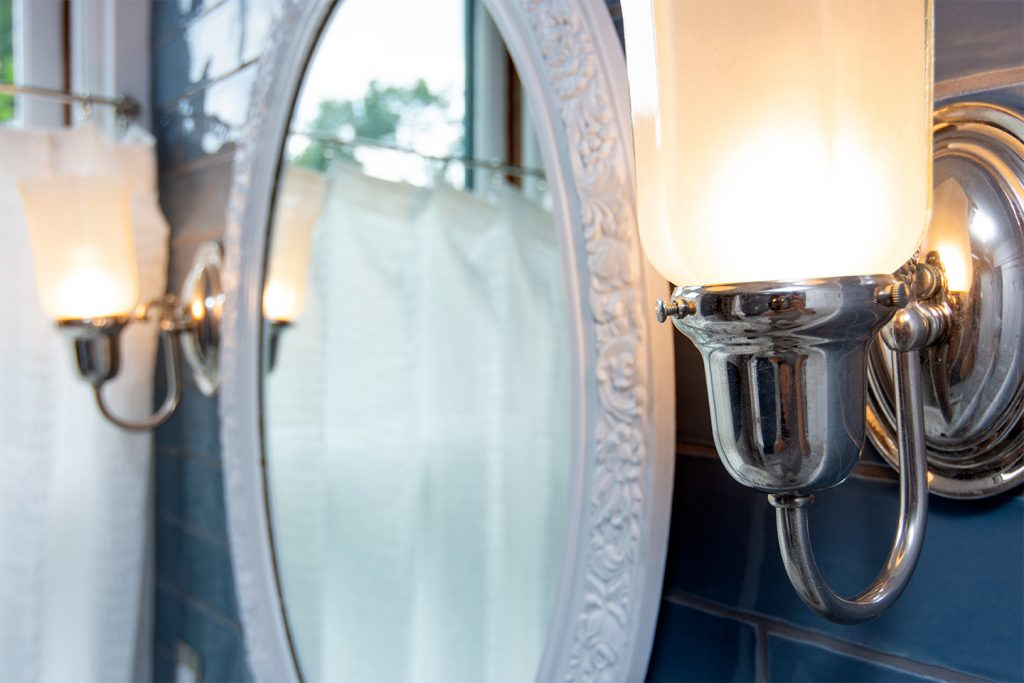 Oval ornate mirror bracketed by fancy tulip-style lamp fixtures.