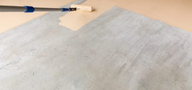 Worker Painting Floor of Garage with Roller.