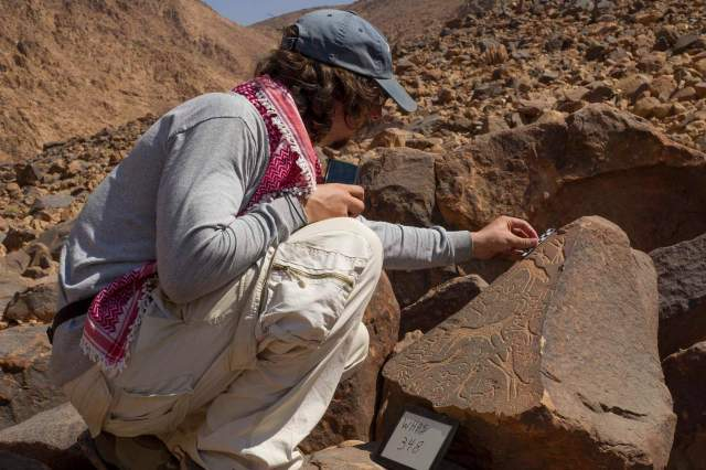 Glenn Corbett places a scale on a stone carved with several Hismaic inscriptions, one of which signs a scene of an ibex hunt. Photo by Michael Fergusson.