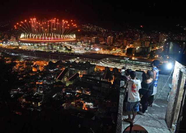 People watch fireworks exploding over the Maracana stadium, from a terrace in the favela Mangueira, during the opening ceremony of the Rio 2016 Olympic Games in Rio de Janeiro on August 5, 2016. / AFP PHOTO / Andrej ISAKOVICANDREJ ISAKOVIC/AFP/Getty Images