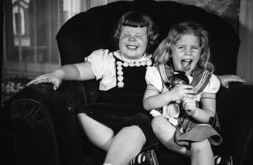 Two Girls Laughing on Chair
