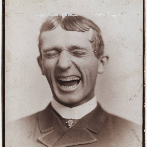 Photo, show business head shot of man laughing with what looks like filed teeth. Scan of 2 d images in the public domain believed to be free to use without restriction in the US.