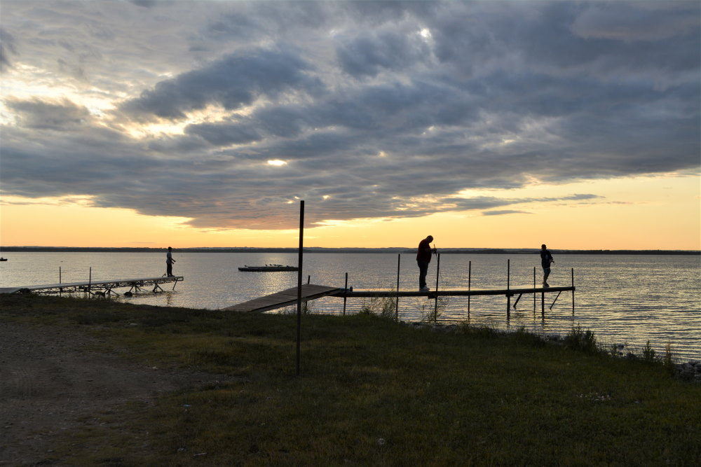 fishing off pier as sun sets across lake