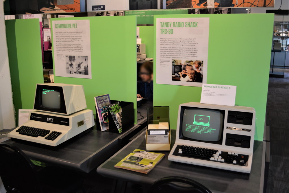 Vintage personal computers sitting on a desk at a museum